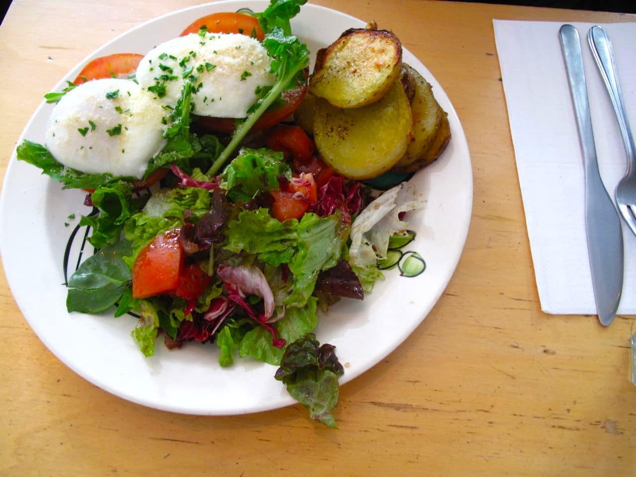 Perfectly poached eggs with fresh green and roasted potatoes.