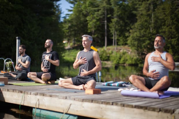 Gay yoga practitioners meditating with Men's Retreats.