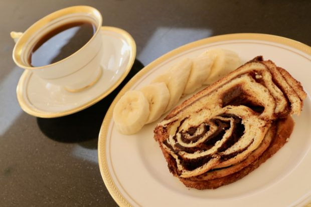 Cinnamon Babka enjoyed at breakfast with a cup of coffee and sliced banana.