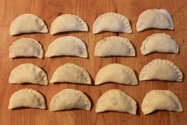Onced filled, homemade pierogies are closed by pinching with your fingers or tines of a fork.