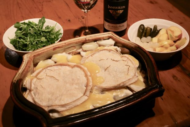 Tartiflette Reblochon served with a dry riesling, arugula salad, gherkins, pickled onions and apple slices.