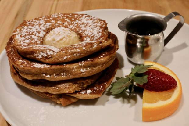 A stack of Gingerbread Pancakes with brown butter and maple syrup.