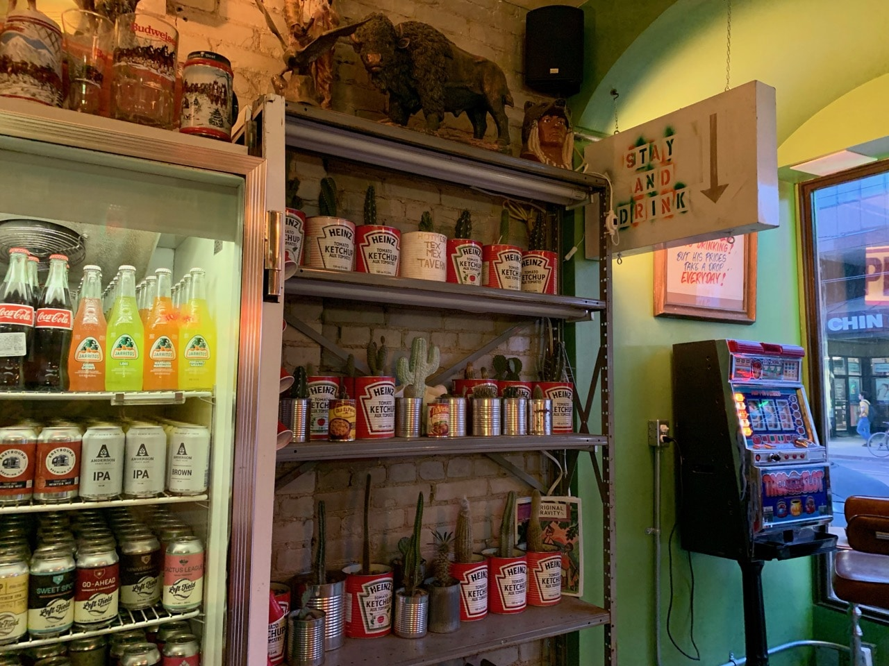 A slot machine and choir of cactus plants in Heinz ketchup containers.