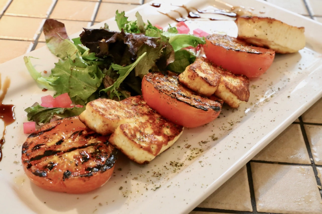 Grilled saganaki cheese is served with tomatoes and balsamic.